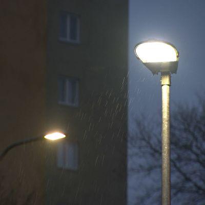 Två gatulampor lyser i regnigt väder.