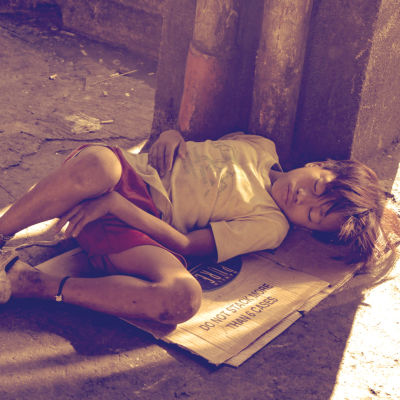 Katulapsi nukkuu Manilan kadulla.