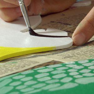 Närbild på pensel som målar detalj på papegojfigur.