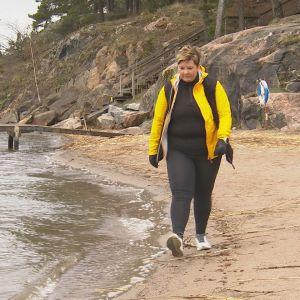 Petra Mannström, en dam med kort hår och gulsvart jacka, går längs en sandstrand med klippor och en livboj i bakgrunden.
