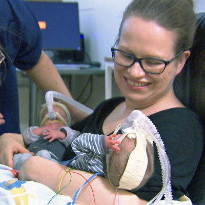 En kvinna håller två små barn (prematurer) i famnen medan hon sitter i en stol. Vid sidan står en sjukskötare och lutar sig så att hon tittar till bebisarna.