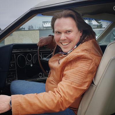 Sami Nieminen istuu autossa ja katsoo avoimen oven kautta hymyillen kameraan.