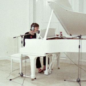 John Lennon soittaa valkoista flyygeliä, Yoko Ono istuu lattialla. Kuva dokumenttielokuvasta John & Yoko: Above Us Only Sky.