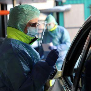 En sjukskötare tar coronavirustest på en person som sitter i en bil.