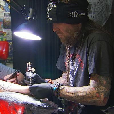 En man i skägg gör en tatuering på baksidan av en annan mans hand.