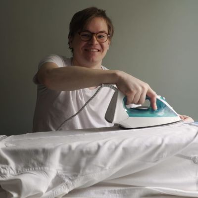 Elias Poutanen ler och stryker sin skjorta