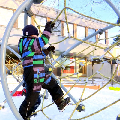 En pojke klättrar i en klätterställning.