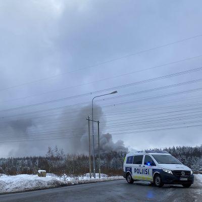 Poliisiauto tiesululla, tulipalon savua taustalla