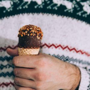 Miehellä on kädessä jäätelötötterö.