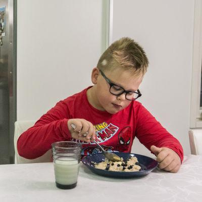 Pojke med glasögon äter frukost
