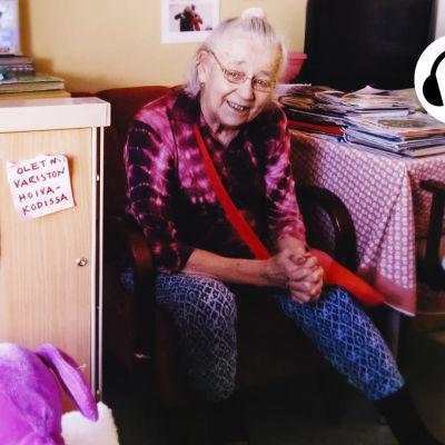 """Aili istuu pöydän ääressä, vieressä olevan kaapin ovessa kuva Ailista Tuula-tyttären kanssa ja lappu jossa lukee """"olen nyt Variston hoivakodissa""""."""