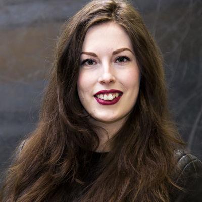 Toimittaja Tuija Siltamäki hymyilee puolilähikuvassa.
