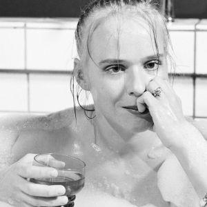 Näyttelijä Leea Klemola istuu kylpyammeessa lasi kädessä.