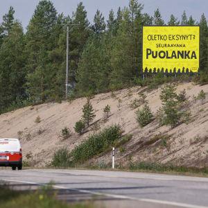 Autotie, jolla ajaa yksi auto. Vieressä hiekkainen sinne ja sen päällä iso keltainen kyltti, jossa lukee 'Oletko eksynyt? Seuraavana Puolanka'.