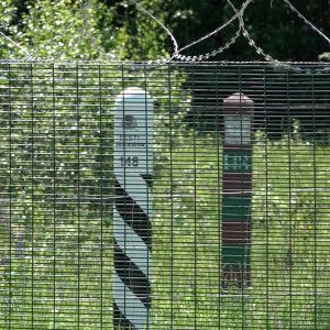 Bakom gränsstaketet syns en estnisk och en rysk gränsstolpe.