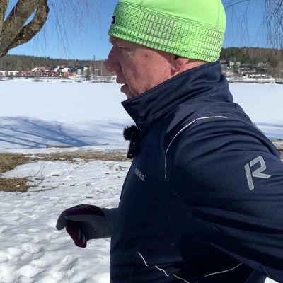 Mies juoksee kevättalvisessa maisemassa
