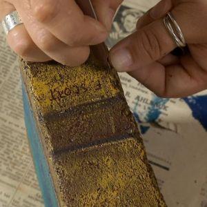 Närbild av detaljer målas in på bokrygg av tegel.