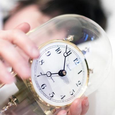 Nainen nukkuu kellon kanssa.