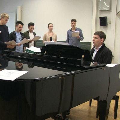 Flyktingar och musikintresserade tyska ungdomar i körövning.
