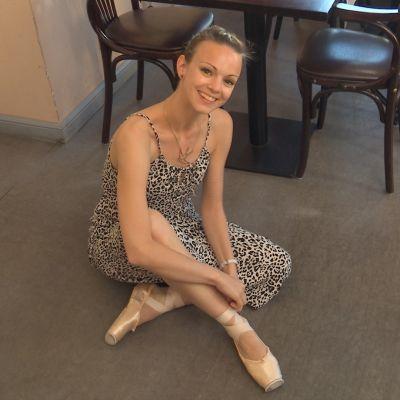 Ballerina Claire Voss sitter på ett cafégolv, brevid sig har hon sin tutu.