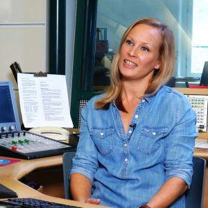 Nainen istuu radiostudiossa.