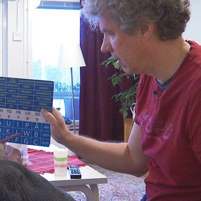 En person håller upp en skylt med bokstäver och ord på, medan en äldre person i rullstol pekar på symbolerna för att kommunicera.