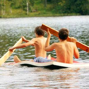 Två pojkar paddlar på egenbyggd flotte.