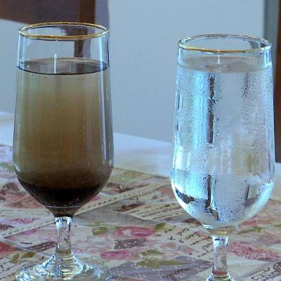 Två glas med svart och klart vatten.