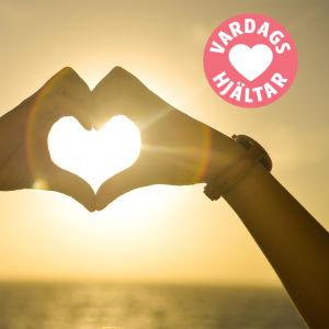 Två händer formar ett hjärta framför solen och vardagshjälte-projektets logo.