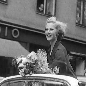 Armi Kuusela vilkuttaa autosta kukkakimppu kädessään. Yleisö on kerääntynyt Helsingin kaduille juhlistamaan Miss Universumia, Armi Kuuselaa.