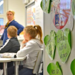Ett barn markerar i en klass där undervisning pågår.