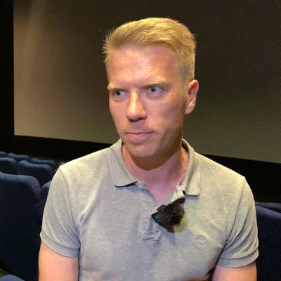 Mies istuu elokuvateatterin penkin käsinojalla valkokangas taustallaan