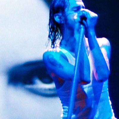 Dave Gahan lavalla, takana iso lähikuva hänestä. Kuva Depeche Moden Devotional-kiertueelta 1993.