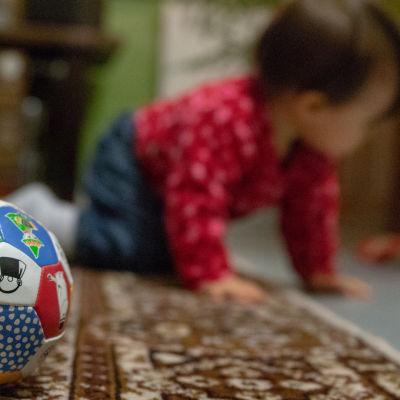 lapsi kontaa lattialla, pallo etualalla