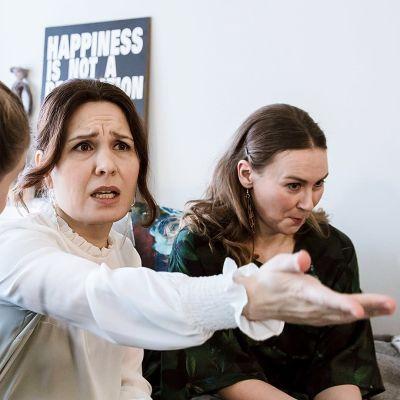 Pirjo istuu sohvalla ja selittää ystävälleen (Kaisla Leppänen) vakava ilme kasvoillaan. Toinen ystävä (Maija Rissanen) pidättelee vieressä nauruaan.