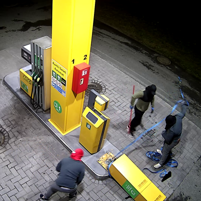 Valvontakamerakuva ylhäältäpäin, kolme kasvonsa peittänyttä varasta on kaatanut tankkausaseman automaatin ja seisovat sen ympärillä.