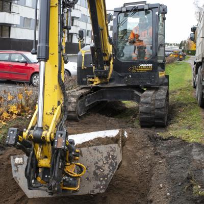 Kaivinkone kaivaa maata kerrostalon parkkipaikan vieressä.