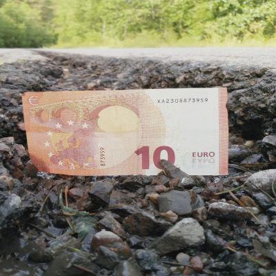 En tio euros sedel i en vägspricka på Ebbovägen i Borgå