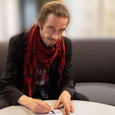 Jarkko Martikainen kirjoittaa nimikirjoitusta.
