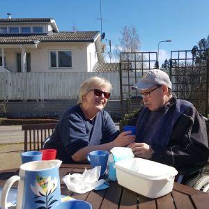 Eeva och Leif Lindell dricker kaffe ute på en solig terass.