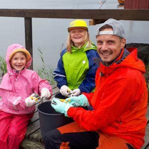 Två flickor och programledaren Jontti klipper fisk i bitar på en brygga