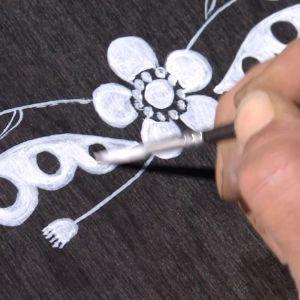 med pensel målas en grafisk bild av en blomma och ett ornament