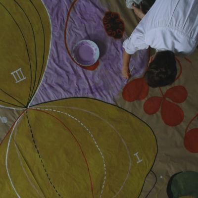 bild uppifrån av konstnären som målar ett av sina enorma verk sittande på golvet.