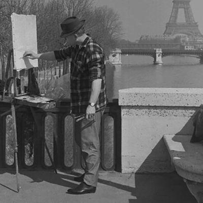 Maalari Seinen rannalla Pariisissa, taustalla Eiffelin torni.