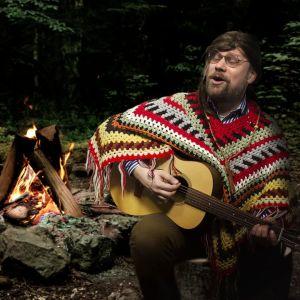 Olli Haapakangas metsässä kitaran kanssa.