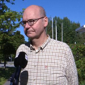 En flintskallig man med glasögon och rutig skjorta står i solen med en mikrofon framför sig.