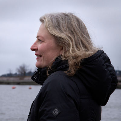 Jessica Haapkylä seisoo sivuttain harmaassa merimaisemassa.