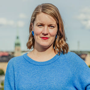 En bild av Marianne SUndholm med en vy över Stockholm i bakgrunden.
