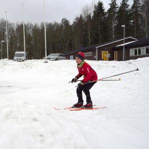 En pojke på skidor kommer till en gupp.