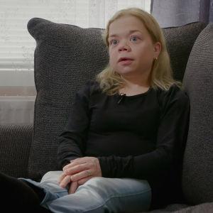 Tuhkimotarinoiden Linda istuu harmaalla sohvalla. Vasemmalla puolella olevassa maljakossa on kimppu punaisia tulppaaneja.